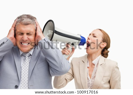Businesswoman screaming with a megaphone after her colleague against white background