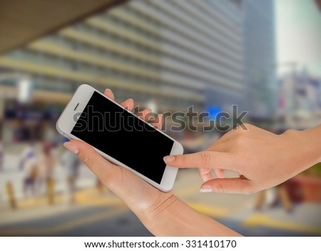 Businesswoman sending messages with her mobile phone, building Background #331410170