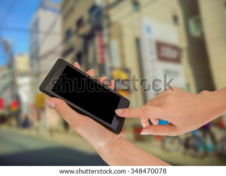 Businesswoman sending messages with her mobile phone, building Background #348470078