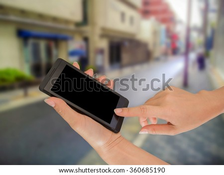 Businesswoman sending messages with her mobile phone, building Background #360685190