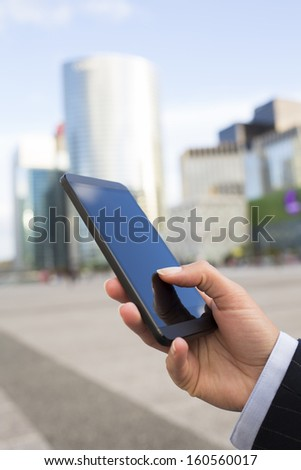 Businesswoman sending messages with her mobile phone in front of building
