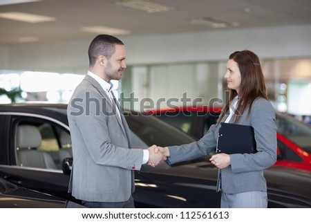 Businesswoman shaking hand of a man in a dealership - stock photo