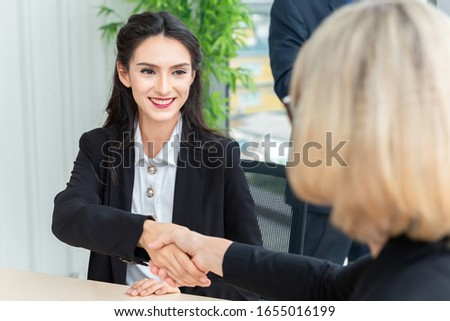 Businesswoman shaking hands with smile while meeting and she get a great deal.