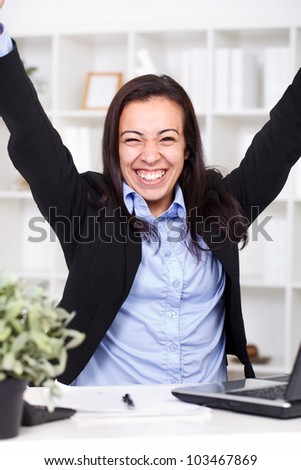Businesswoman showing her victory with raised hands in office