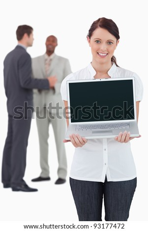 Businesswoman showing laptop with colleagues behind her against a white background