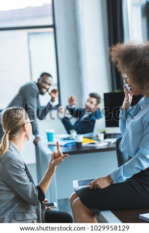 businesswoman showing middle finger to colleagues in office