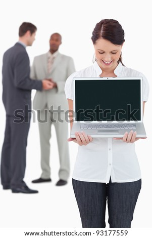 Businesswoman showing notebook with colleagues behind her against a white background