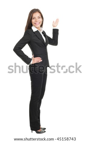 Businesswoman showing / pointing at copy space in full length. Confident mixed race chinese / caucasian woman isolated on white background.
