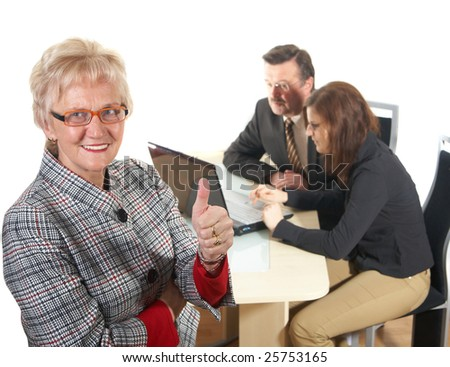 Businesswoman showing thumb up sign in office environment. Three people with focus on mature woman in front. Isolated over white.
