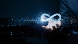 Businesswoman shows sign of infinity on the background of the city. The concept of unlimited Internet.
