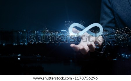 Businesswoman shows sign of infinity on the background of the city. The concept of unlimited Internet. #1178756296