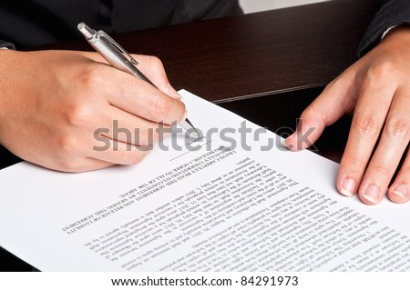 Businesswoman signing a document.