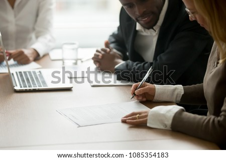 Businesswoman signing business document at meeting with african partners, satisfied client customer agreeing to put signature on contract agreement buying services or taking bank loan, close up view