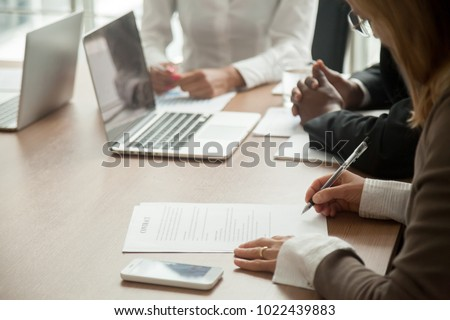 Businesswoman signing contract making legal deal with multiracial partners in bank, woman putting written signature on business document, taking commercial loan or insurance concept, close up view