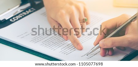 Businesswoman signs agreement contract with another businesswoman at the office. Concept of business partnership and legal agreement of lawyer. #1105077698
