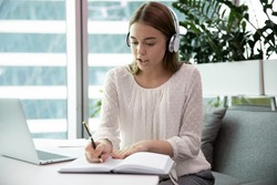 Businesswoman sit at desk in wireless headphones learn language listen lecture study online with teacher, watch webinar write notes, distant education, business conference with company clients concept