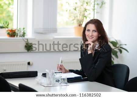 Businesswoman sits at a table in a meeting room