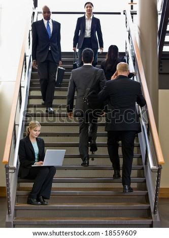 Businesswoman sitting and working on laptop on busy office stairs