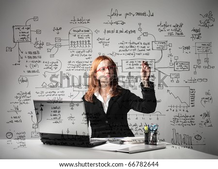 Businesswoman sitting at a desk in front of a laptop and drawing some schemes