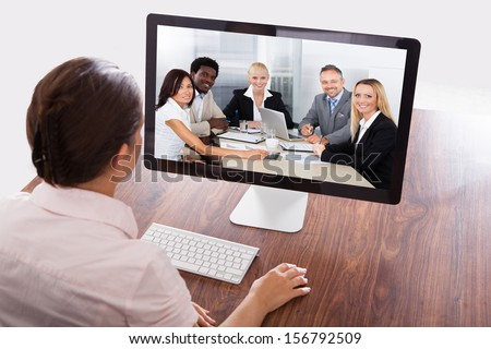 Businesswoman Sitting At A Desk Watching An Online Presentation On The Computer