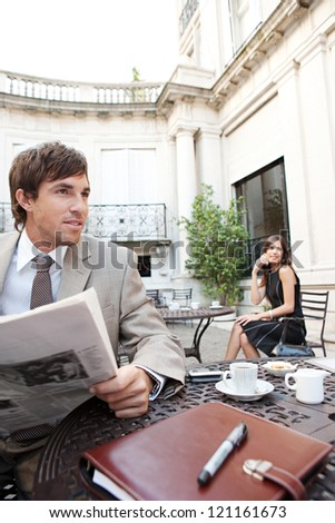 Businesswoman sitting at coffee shop terrace having a cell phone conversation while a businessman sits reading a newspaper in a classic city financial district with office buildings around them.