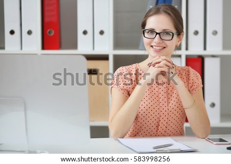 Businesswoman sitting at table in office. He looks at the camera and smiling.