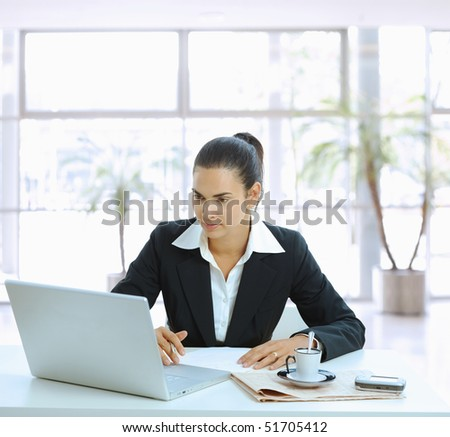 Businesswoman sitting at table in office lobby and using laptop computer.