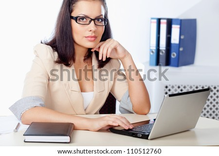 businesswoman sitting behind the desk working  with notebook
