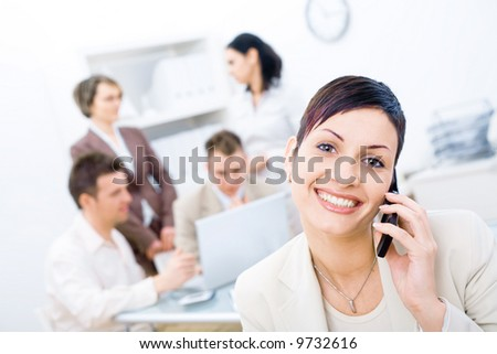 Businesswoman sitting in front, calling on phone, looking at camera, smiling. Four business colleagues working on laptop computer in background.