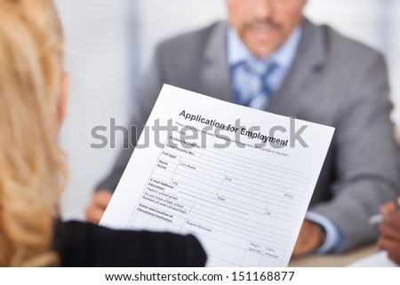 Businesswoman Sitting In Front Of Businessman Holding Application Form