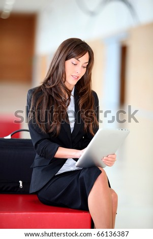 Businesswoman sitting in hall with electronic pad