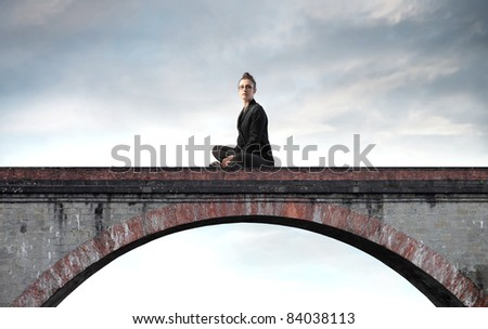 Businesswoman sitting on a bridge