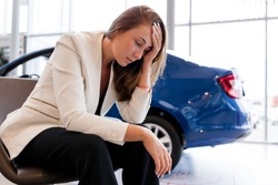 Businesswoman sitting on a chair holding his head from the problems on the background of the car. Confiscation of the car for tax evasion