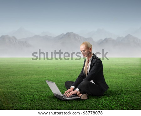 Businesswoman sitting on a green meadow and using a laptop