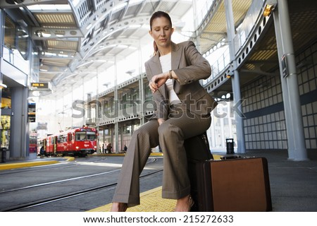 Businesswoman sitting on suitcase, waiting for city tram, checking time on wristwatch (surface level)
