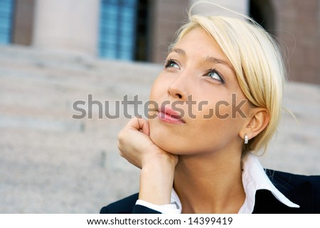 Businesswoman sitting outside building contemplating, close-up