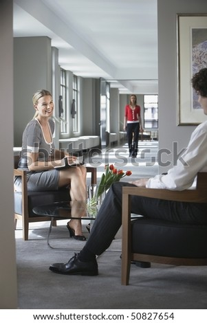 Businesswoman sitting talking to businessman in office