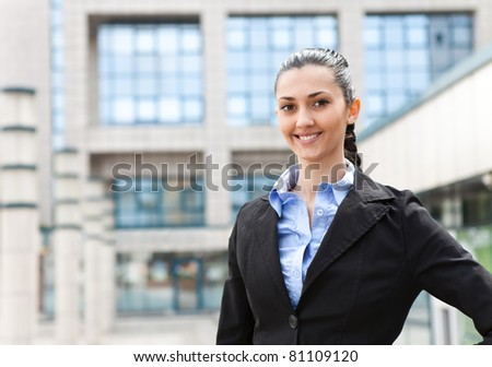 businesswoman smiling at the camera while standing in front of an office building, horizontal shot