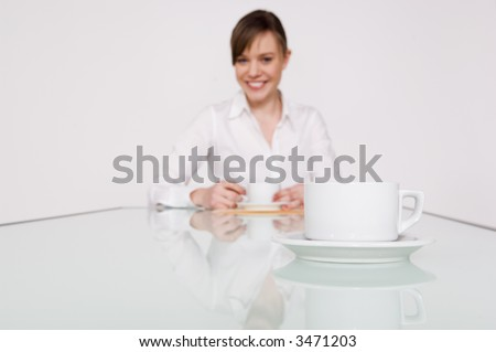 Businesswoman smiling in soft focus with a cup of coffee in the foreground.