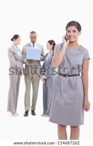 Businesswoman smiling on the phone and looking straight ahead with one arm along her body and co-workers in the background
