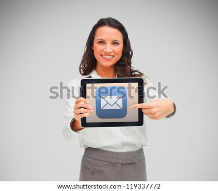 Businesswoman smiling while holding a tablet computer and pointing to mail symbol against grey background