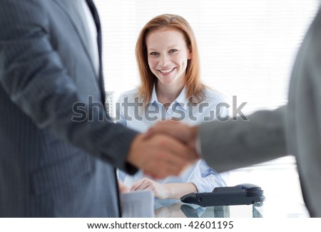 Businesswoman smiling with businessmen greeting each other in the foreground at a job interview