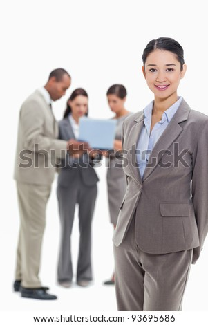 Businesswoman smiling with co-workers watching a laptop in the background against white background