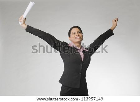 Businesswoman smiling with her arms raised