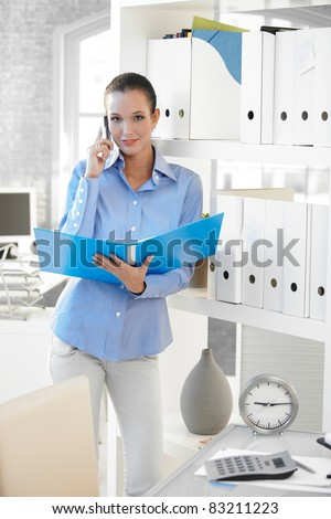 Businesswoman speaking on cellphone, holding folder, smiling confidently at camera.?