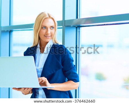 Businesswoman standing against office window holding laptop #376462660