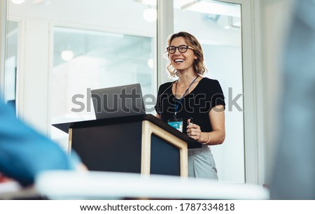 Businesswoman standing at podium with laptop giving a speech. Successful female business professional addressing a seminar.