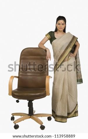 Businesswoman standing beside an office chair - stock photo