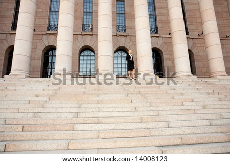 Businesswoman standing by building, wide angle view