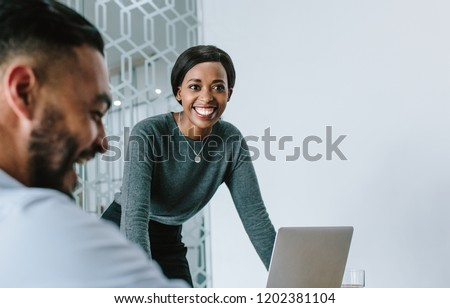 Businesswoman standing by her laptop and smiling during a board room meeting. Smiling woman giving presentation to her team in conference room. #1202381104